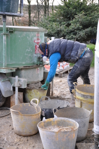 Mixing hempcrete in a large pan mixer. This is the usual method since large quantities are easily mixed.
