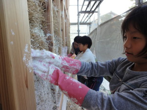 The exterior side of the bale wall is plastered and allowed to dry before covering with a ventilated rain screen.