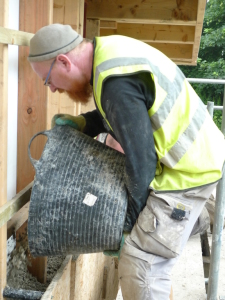 Tipping hempcrete into the shuttering.