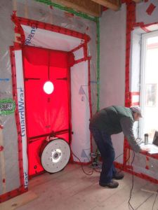 Blower door test. A blower door is used to find points of air leakage into a building.
